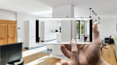 Two hands holding a Smartphone taking a picture in a newly remodeled luxury living room and kitchen