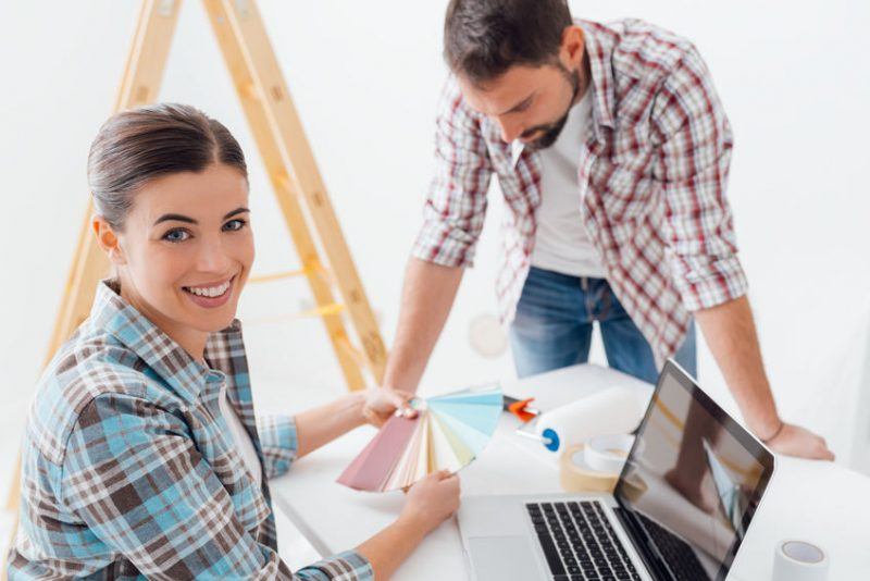 Young couple renovating their home, choosing paint colors